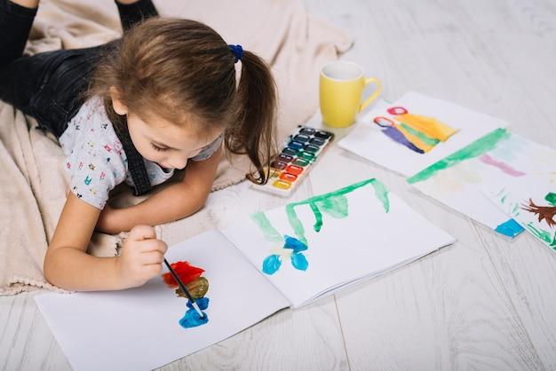 Linda chica pintando con brillante acuarela en el piso