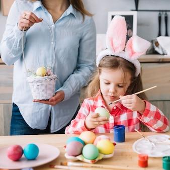 Linda chica pintando huevos para pascua cerca de la madre con una canasta pequeña
