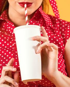 Linda chica pinup bebiendo refrescos