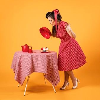 Linda chica pinup de pie junto a unos cupcakes