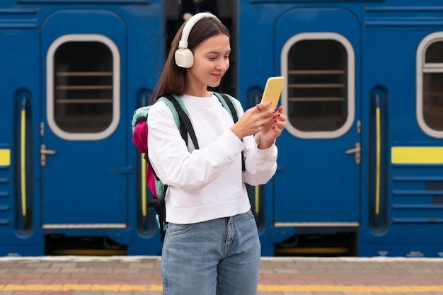 Linda chica en el plano medio de la estación de tren