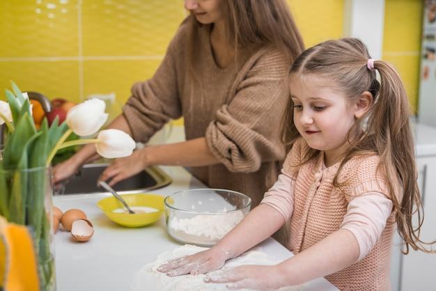 Linda chica poniendo harina en la mesa