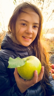 Linda chica posando con manzana verde al aire libre
