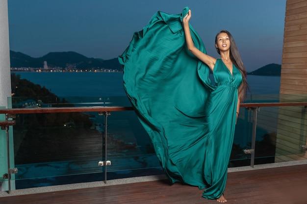 Linda chica posando en la terraza con un hermoso vestido de noche de color azul levantando la esquina del vestido