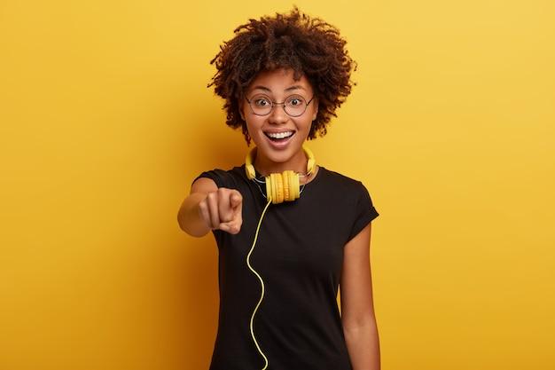 Linda chica positiva de piel oscura usa camiseta negra, gafas redondas, tiene auriculares amarillos conectados a algún dispositivo, siendo meloman real