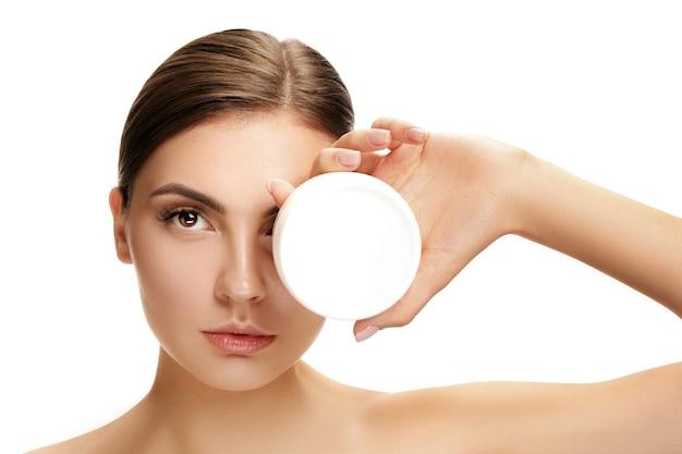 Linda chica preparándose para comenzar su día. ella está aplicando crema humectante en la cara. el concepto de belleza, cuidado, piel, tratamiento, salud, spa, cosmética y publicidad