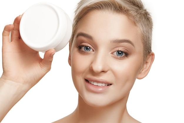 Linda chica preparándose para comenzar su día. ella está aplicando crema humectante en la cara. el cuidado, la piel, el tratamiento, la salud, el spa, el concepto cosmético.
