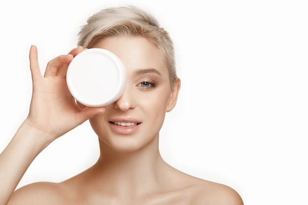 Linda chica preparándose para comenzar su día. ella está aplicando crema humectante en la cara.