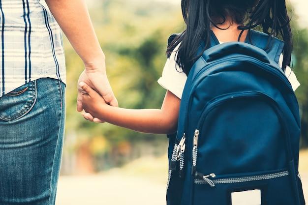 Linda chica de pupila asiática con mochila sosteniendo su mano de madre e ir a la escuela