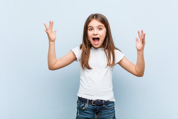 Linda chica recibiendo una agradable sorpresa, emocionada y levantando las manos.