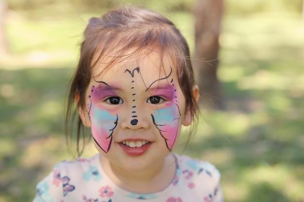 Linda chica recibiendo cara pintada como una mariposa