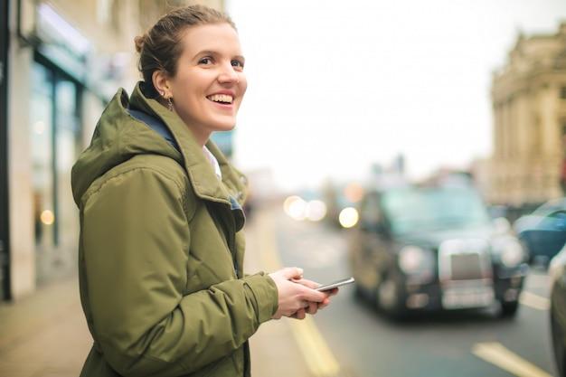 Linda chica revisando su teléfono inteligente mientras camina en la calle