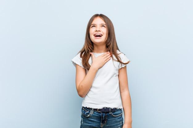Linda chica se ríe a carcajadas manteniendo la mano en el pecho.
