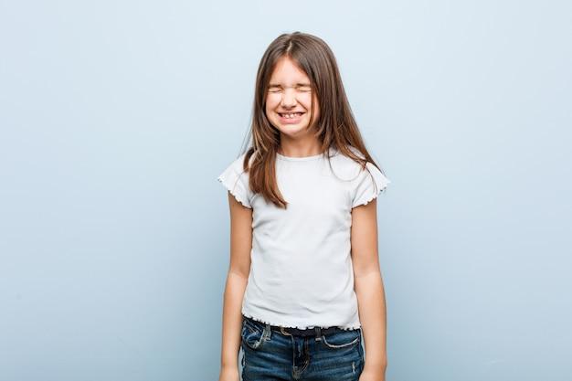 Linda chica se ríe y cierra los ojos, se siente relajada y feliz.