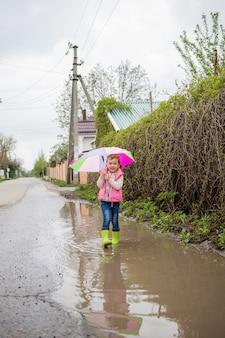 Una linda chica se ríe con un paraguas y botas de goma verde. la niña está caminando a través de un gran charco.