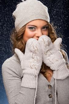 Linda chica rizada con guantes durante las nevadas