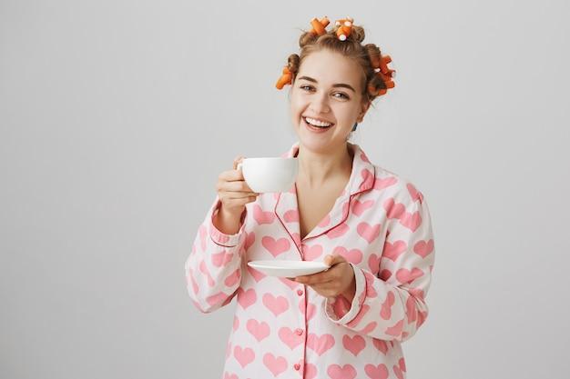 Linda chica en rizadores de pelo y pijama bebiendo una taza de té y sonriendo