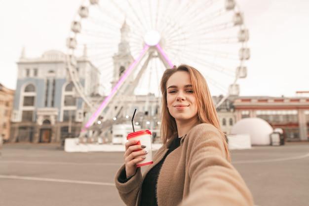 Linda chica en ropa de primavera, vistiendo un abrigo, sosteniendo una taza de café en la mano y toma selfie en el fondo de la calle