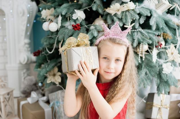 Linda chica rubia de 5 años con caja de regalo de navidad cerca del árbol de navidad.