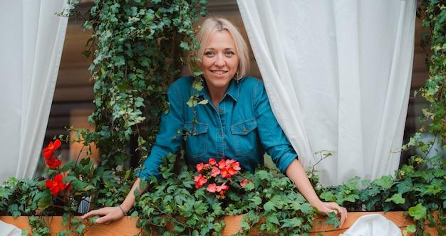 Linda chica rubia en el balcón con flores disfrutando de la vista y el aire fresco.