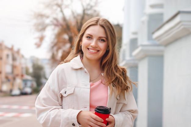 Linda chica rubia está caminando en la ciudad con una taza de café y sonriendo