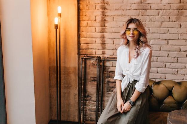 Linda chica rubia con camisa blanca sentada en un sofá de cuero en una habitación con diseño loft y mira con interés
