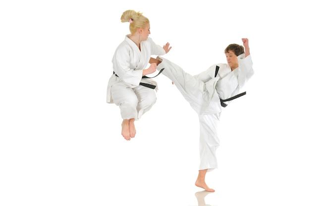 Linda chica rubia y un joven chico descarado de karate se dedican a la formación en un kimono sobre un fondo blanco.