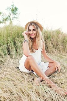Linda chica rubia de longitud completa con cabello largo está posando para la cámara sobre pasto seco. lleva sombrero, vestido blanco y sonríe a la cámara.