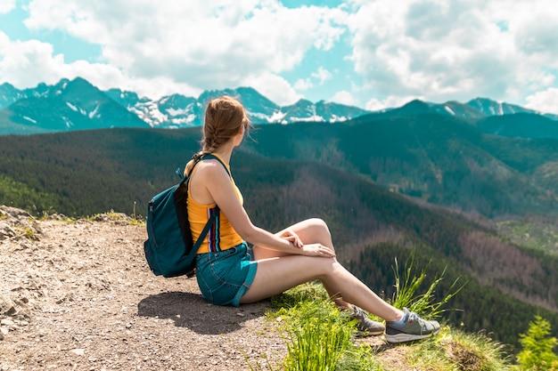 Linda chica rubia con una mochila y gafas se sienta en una montaña y disfruta de las hermosas colinas de las montañas en un día soleado.