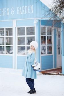 Una linda chica rubia va a patinar al aire libre. una niña en un abrigo azul y sombrero de piel con patines en la casa de invierno. actividades de fin de semana en climas fríos. navidad, concepto de vacaciones de invierno. deporte de invierno.