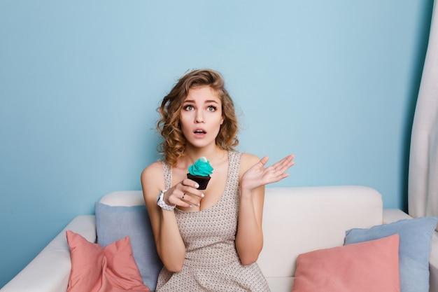 Linda chica rubia con pelo rizado sentada en un sofá y sosteniendo una magdalena azul.
