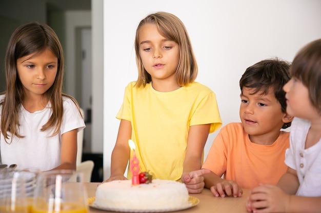 Linda chica rubia pidiendo deseos y celebrando su cumpleaños con amigos. niños encantadores de pie juntos en la habitación y mirando sabroso pastel con vela. concepto de infancia, celebración y vacaciones.