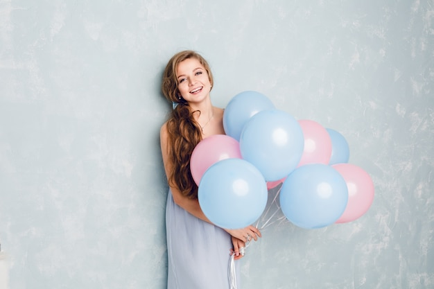 Linda chica rubia de pie en un estudio, sonriendo y sosteniendo globos azules y rosados.