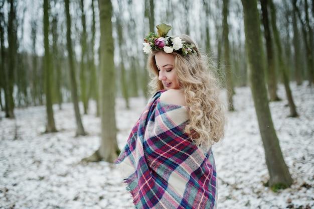 Linda chica rubia rizada con corona en cuadros cuadros en bosque nevado en día de invierno.