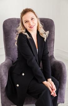 Una linda chica rubia con un traje negro está sentada en una silla, sonriendo y mirando a la cámara.