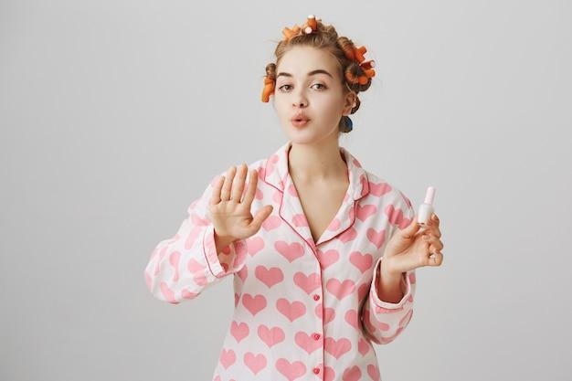 Linda chica con rulos en el pelo y pijama, esmalte de uñas