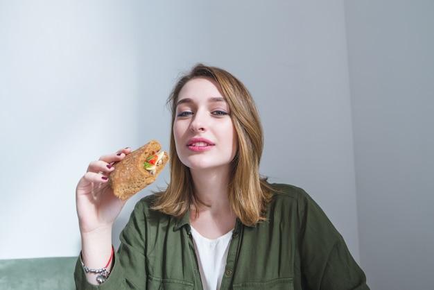 Linda chica con sandwich en sus manos mira camerand sonrisas. mujer desayuna comida rapida