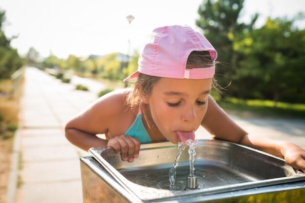 Linda chica sedienta bebe agua del fregadero