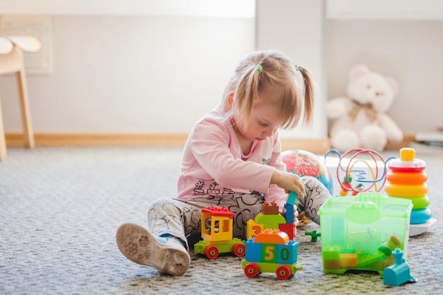 Linda chica sentada en la alfombra jugando