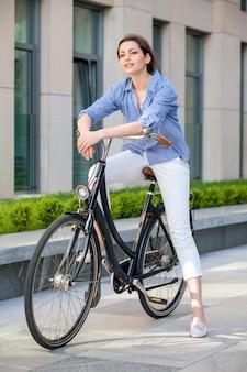 Linda chica sentada en una bicicleta en la calle