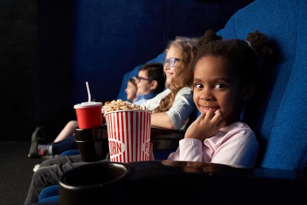 Linda chica sentada en el cine con amigos, mirando a cámara.