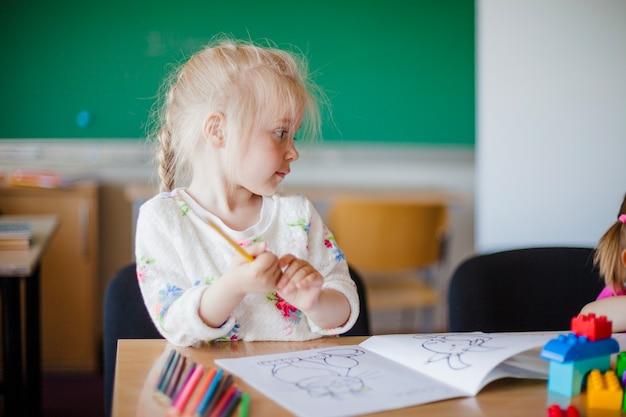 Linda chica sentada a la mesa en el aula