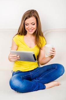 Linda chica sentada con las piernas cruzadas y leyendo noticias en su tablet pc