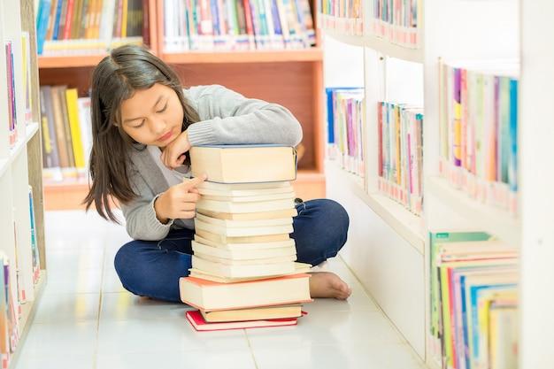 Linda chica sentada en el piso y muchos libros