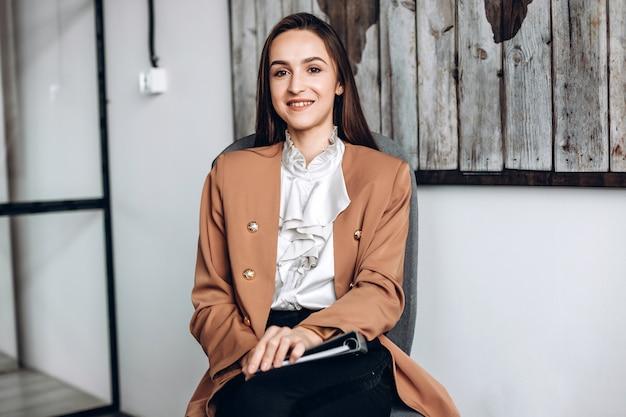 Linda chica sentada en una silla, trabajando en la oficina