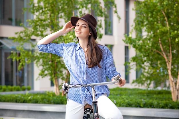 Linda chica en sombrero montando una bicicleta en la calle