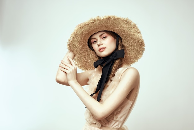 Linda chica con sombrero de paja con cinta negra y vestido sobre fondo claro vista recortada