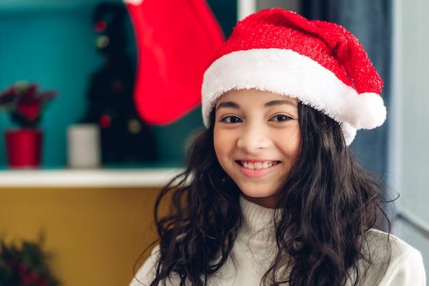 Linda chica con sombreros de santa sonriendo y mirando a cámara mientras celebraba la víspera de año nuevo