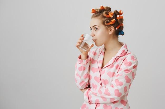 Linda chica soñadora en agua potable de ropa de dormir, usando rizadores de pelo