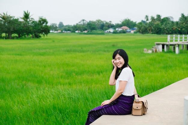 Linda chica sonríe en el campo de arroz, tailandia